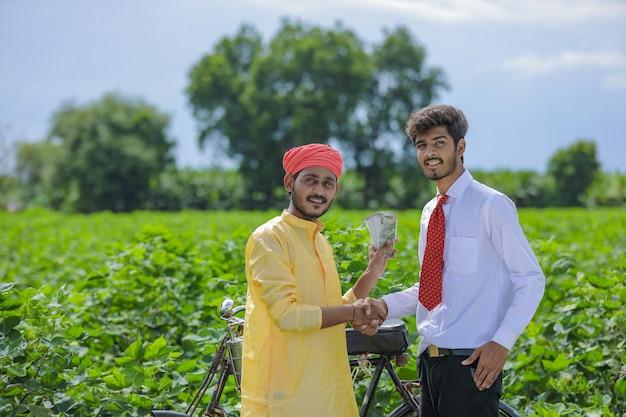 フィールドに立っているインドの農民と銀行家