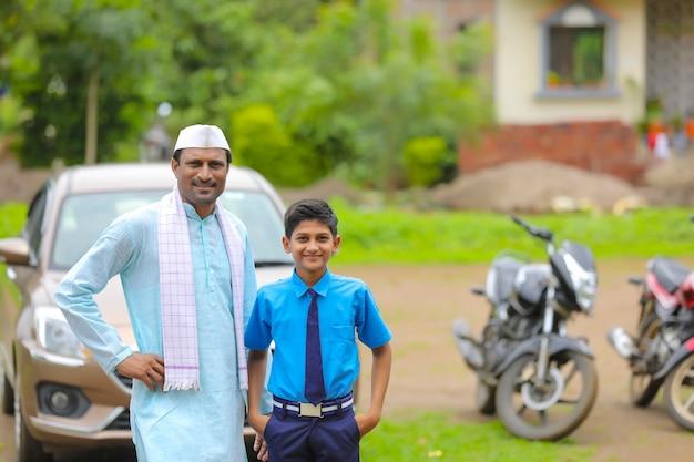 インドの農夫と彼の子供は彼の新しい車で立っています