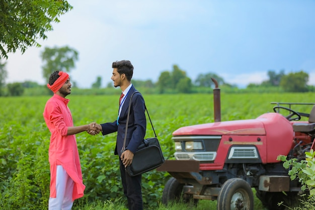 Indian farmer and banker standing at field
