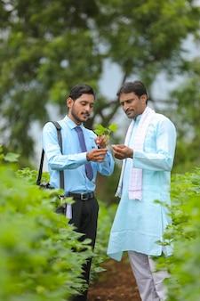 Индийский фермер обсуждается с агрономом на ферме и собирает некоторую информацию