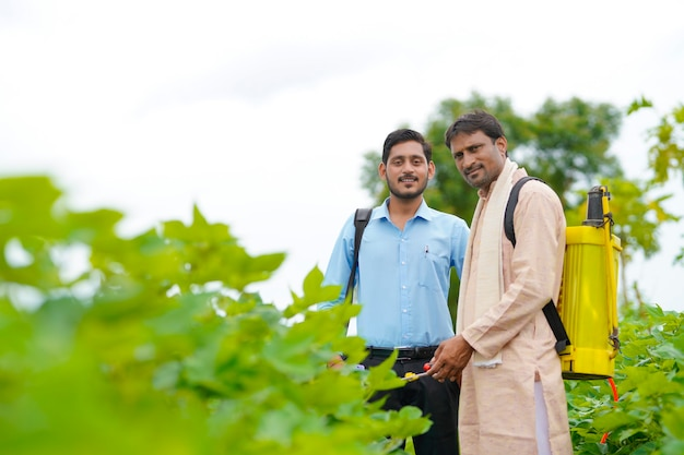 Indian farmer discussing with agronomist at farm and collecting some information