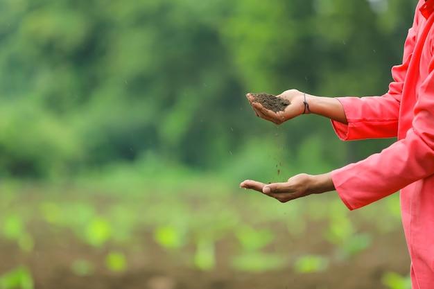 Индийский фермер держит в руках чернозем