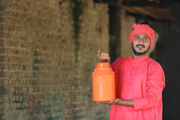 酪農場で牛乳瓶を手に持っているインドの農民