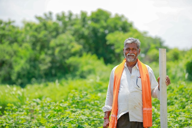 Indian farmer holding pipe at cotton field.