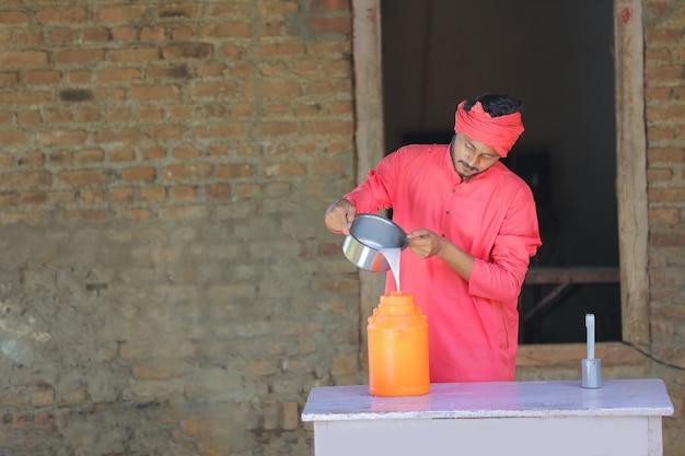 酪農場で牛乳を集めるインドの農民または牛乳配達人