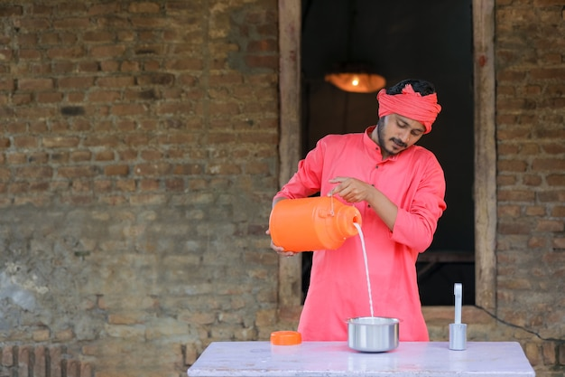 인도 농부 또는 우유 배달원이 낙농장에서 우유를 배포합니다.
