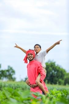 Индийский фермер играет со своим ребенком на зеленом поле