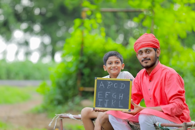 Indian farmer showing a b c d alphabet on chalkboard with his child