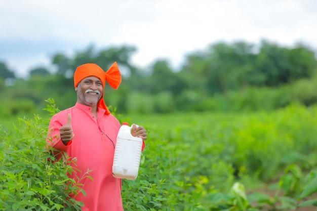 フィールドで肥料瓶を示すインドの農民