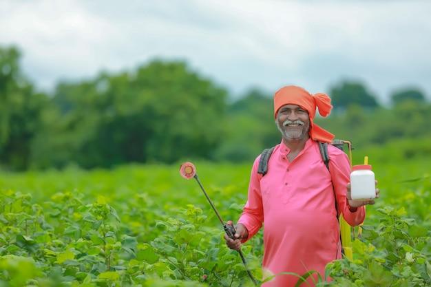 Индийский фермер показывает бутылку удобрений на поле