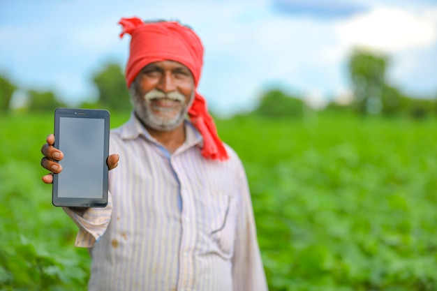 Indian farmer showing a mobile screen at agriculture field