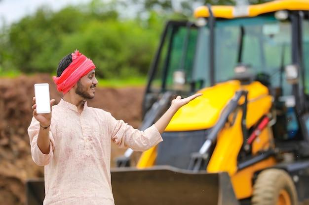 彼の新しい土工機械機器でスマートフォンを示すインドの農民