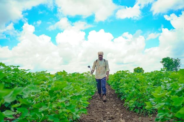 綿花畑で農薬を散布するインドの農民
