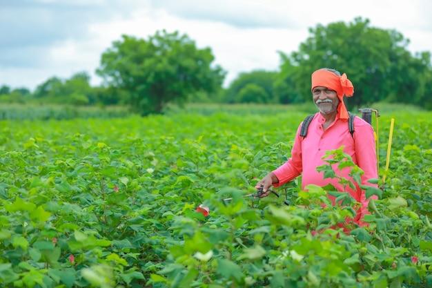 Индийский фермер распыляет пестициды на хлопковом поле