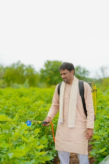 Indian farmer spraying pesticide at cotton field.