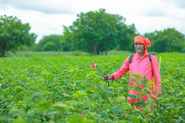Indian farmer spraying pesticide at cotton field