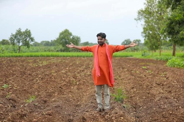 農業分野で立って手を広げているインドの農民。