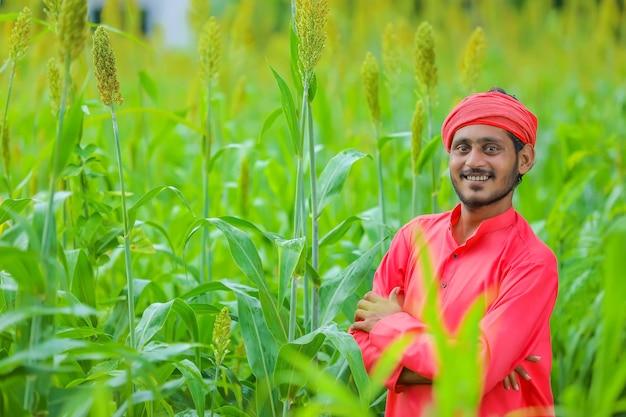 Indian farmer standing in sorghum field