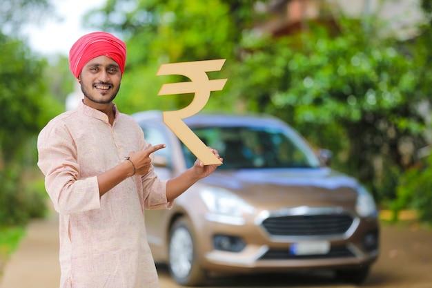 車を持って立ってルピー記号を示すインドの農民