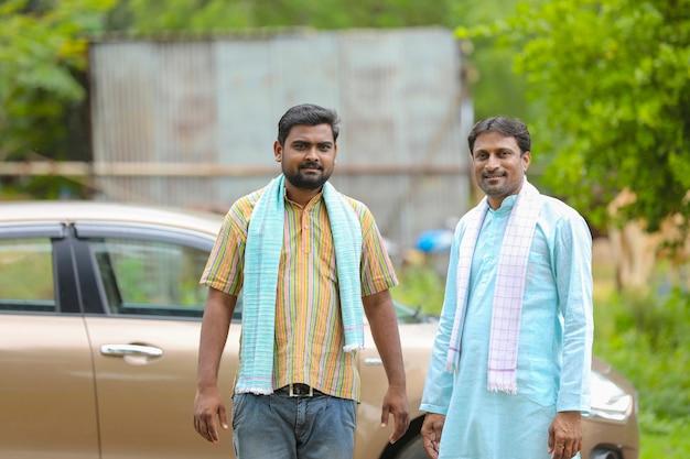 彼の新しい車で立っているインドの農夫