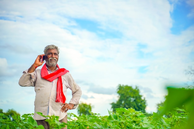Indian farmer talking on mobile phone at agriculture field