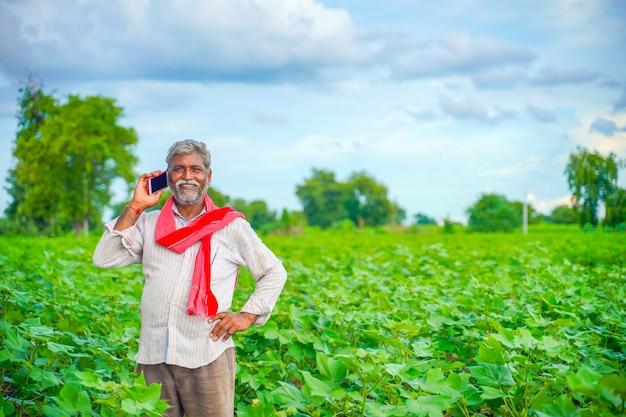 農業分野で携帯電話で話しているインドの農家