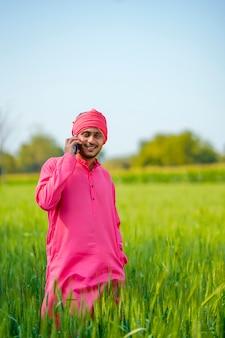 緑の麦畑でスマートフォンで話しているインドの農民