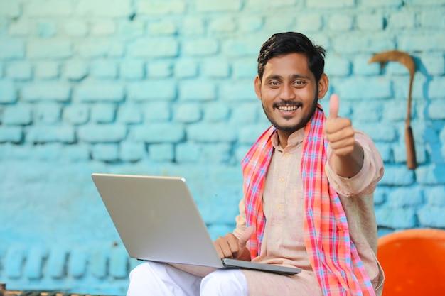 Индийский фермер с помощью ноутбука и показывает бугорки дома.