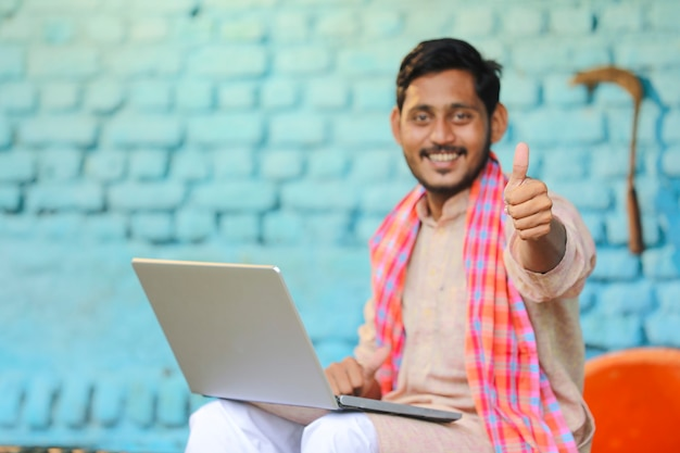 Indian farmer using laptop and showing thumps up at home.