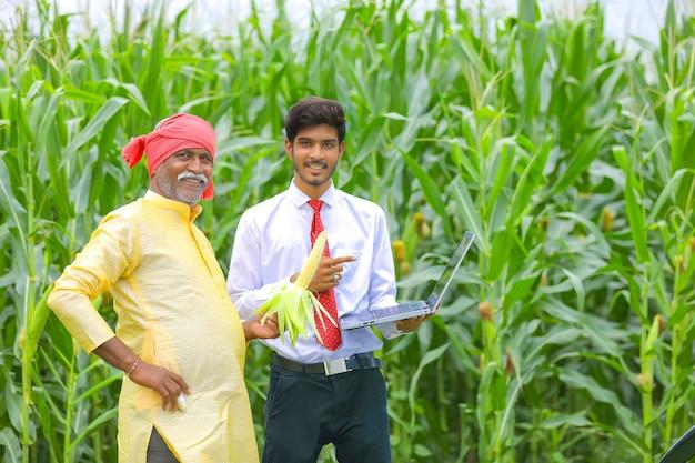 トウモロコシ畑で農学者とラップトップでいくつかの情報を示しているインドの農民