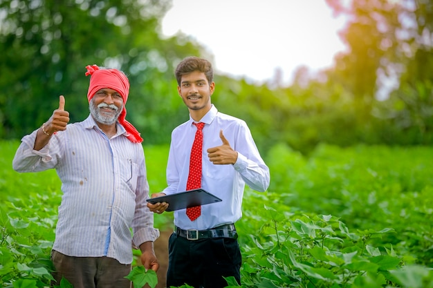 Indian farmer with agronomist at cotton field , showing thumbs up