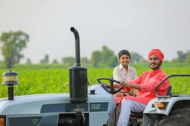 Индийский фермер со своим маленьким ребенком работает с трактором на поле