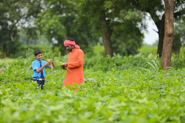 Indian farmer with his son at agriculture field