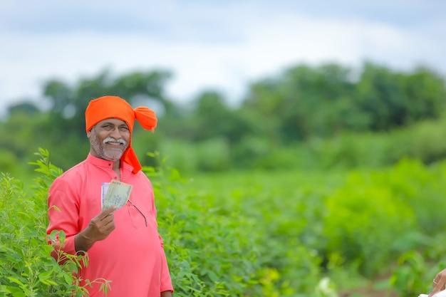 お金とタブレットを持つインドの農民