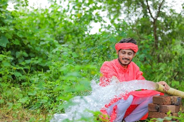 フィールドでパイプからの水流を持つインドの農民