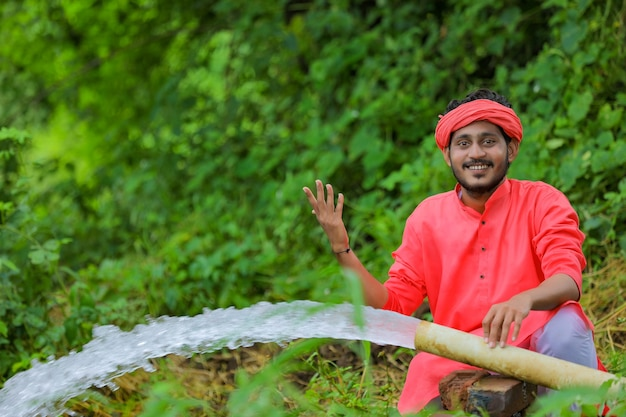 Indian farmer with water flow from pipe at field