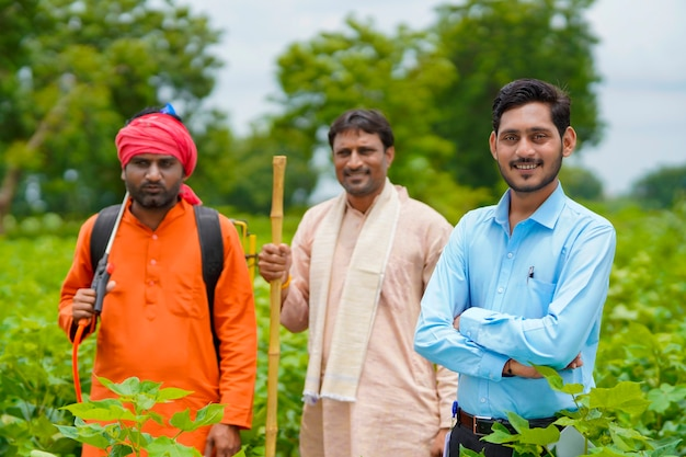 Indian farmers standing with agronomist or bank officer