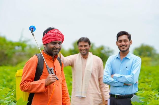 농업 경제학자 또는 은행 직원과 함께 서 있는 인도 농부