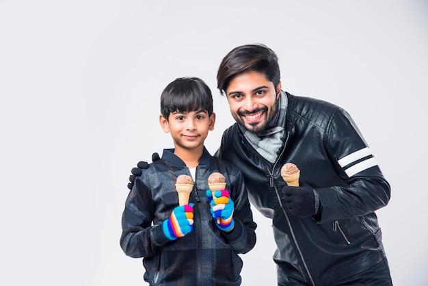 Индийский отец и сын едят мороженое в теплой одежде на белом фоне