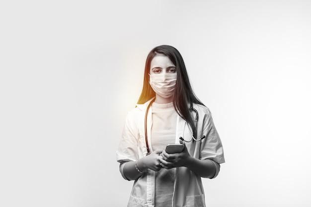 スマートフォンで話しているインドの女性医師が興奮し、コロナウイルスのパンデミックで医療マスクを着用