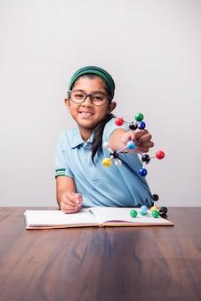 과학, 선택적 초점을 공부하기 위해 분자 모델 키트를 사용하는 인도 여학생