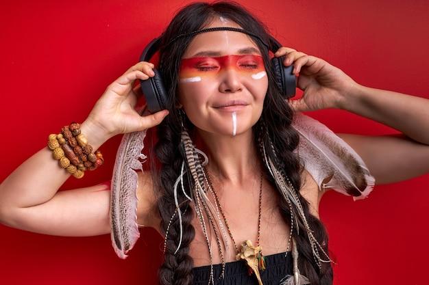 ヘッドフォンを使用しているインドの女性、シャーマニズムの女性はその中の音楽が好きで、赤い壁に隔離された目を閉じて音楽を聴く
