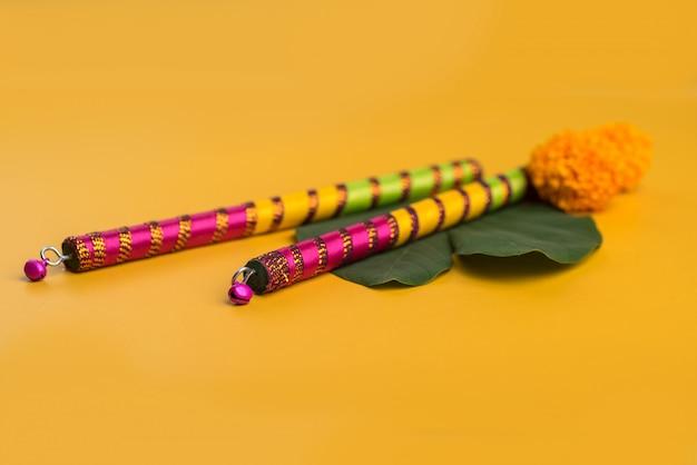 Индийский фестиваль dussehra и navratri, показывающий золотой лист (bauhinia racemosa) и цветы календулы с палочками дандия.