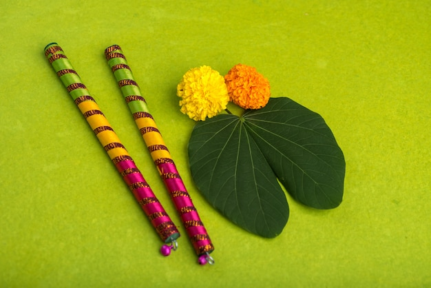 Indian festival dussehra and navratri, showing golden leaf (bauhinia racemosa) and marigold flowers with dandiya sticks on a green background
