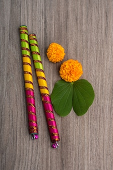 Indian festival dussehra and navratri, showing golden leaf (bauhinia racemosa) and marigold flowers with dandiya sticks on a wooden background