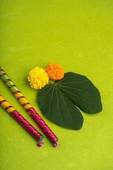Indian festival dussehra and navratri, showing golden leaf and marigold flowers with dandiya sticks on green