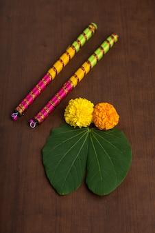 Indian festival dussehra and navratri, showing golden leaf and marigold flowers with dandiya sticks.