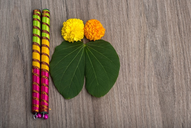 Indian festival dussehra and navratriand marigold flowers with dandiya sticks on a wooden background