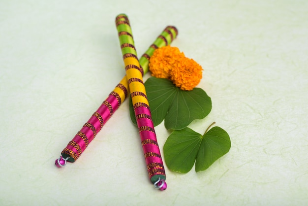 Indian festival dussehra, showing golden leaf (bauhinia racemosa) and marigold flowers with dandiya sticks.