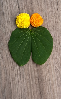Indian festival dussehra, showing golden leaf (bauhinia racemosa) and marigold flowers on a wooden background.